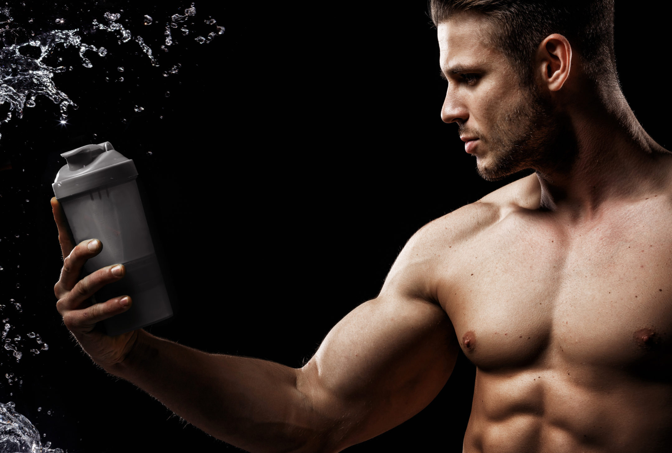 Model sports young man on dark background. Portrait of beautiful strong muscle guy with gray protein drink in shaker. Water splash.